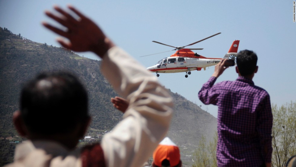 People in Doda wave as a helicopter carrying Gandhi leaves after a campaign rally on April 11.