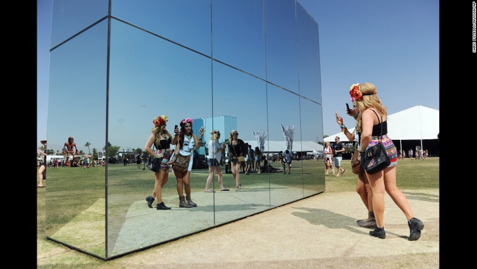 People take selfies near a mirror art installation on April 13.