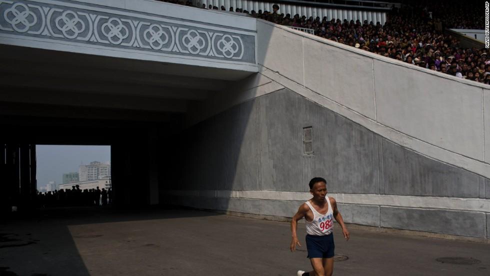 An elderly North Korean man enters Kim Il Sung Stadium on the last stretch of his run.