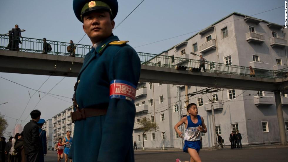 Runners pass under a pedestrian bridge in central Pyongyang as an official keeps watch.