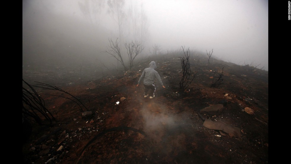 A person walks through the burnt remains of a hill Tuesday, April 15, after a wildfire burned through areas of Valparaiso, Chile. Authorities say the fire in Valparaiso and the suburb of Vina del Mar destroyed hundreds of homes, claimed several lives and forced thousands to evacuate.