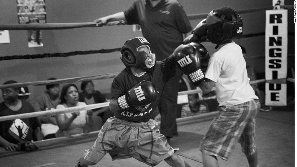Twelve-year-old Deville, left, lands a punch on 11-year-old Andre at the Englewood Crushers Club in Chicago during a boxing demonstration on June 7, 2013, attended by parents and the community. Sally Hazelgrove founded the Crushers Club to get kids off the streets in Englewood, one of Chicago's most depressed and violent neighborhoods.