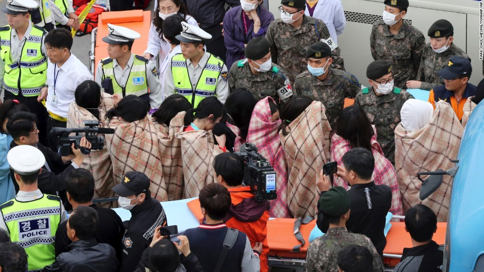 Officials escort rescued passengers April 16 in Jindo.