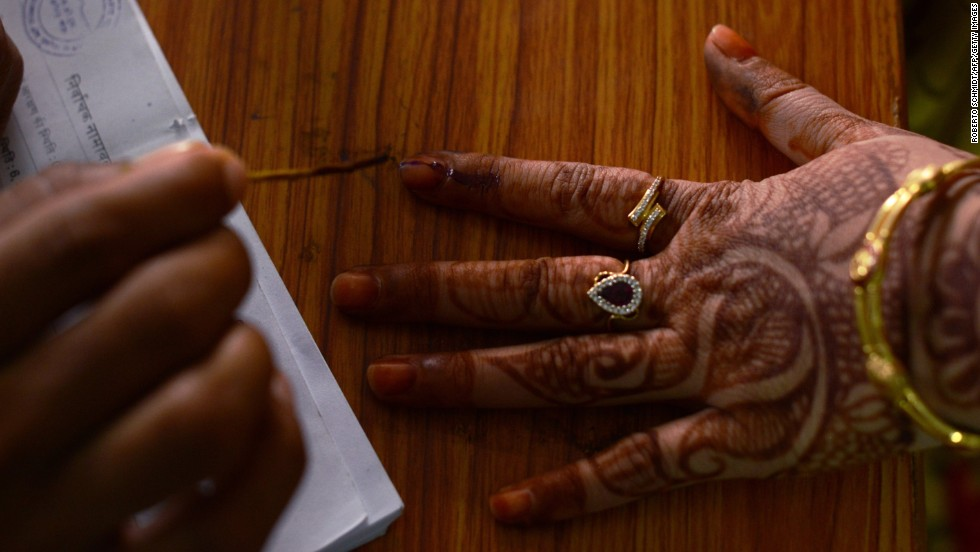An Indian election official marks the finger of a voter with ink before she casts her ballot in Sambhar, India, on April 17.