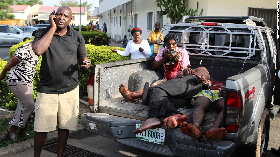 "Injured victims of a <a href=""http://www.cnn.com/2014/04/14/world/gallery/nigeria-bus-station-blast/index.html"">bomb attack</a> wait in the back of a pickup truck near a hospital in Abuja, Nigeria, on Monday, April 14. Dozens of people were killed and more than 100 were injured after a parked vehicle exploded at the Nyanya Motor Park bus station, Nigerian officials said."