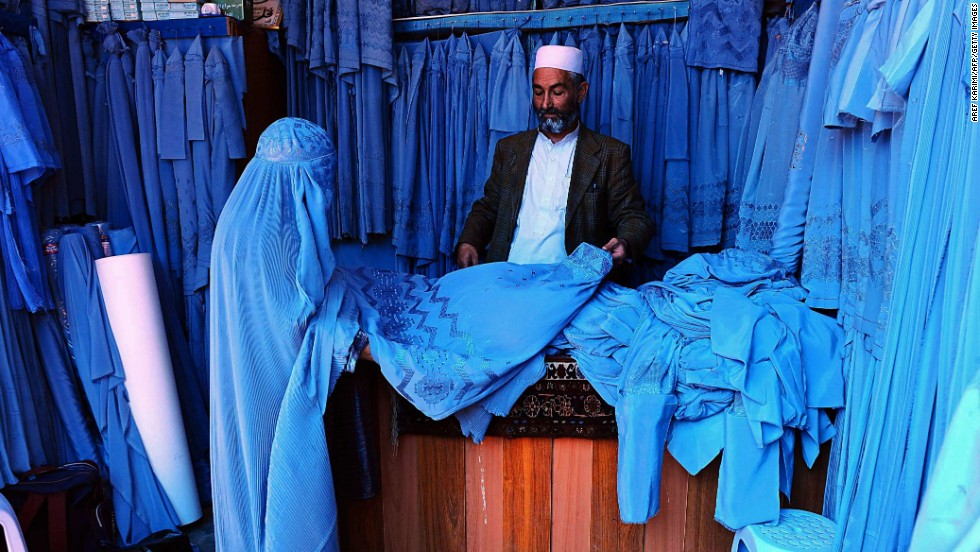 An Afghan shopkeeper shows a burqa to a customer in Herat, Afghanistan, on Sunday, April 13.
