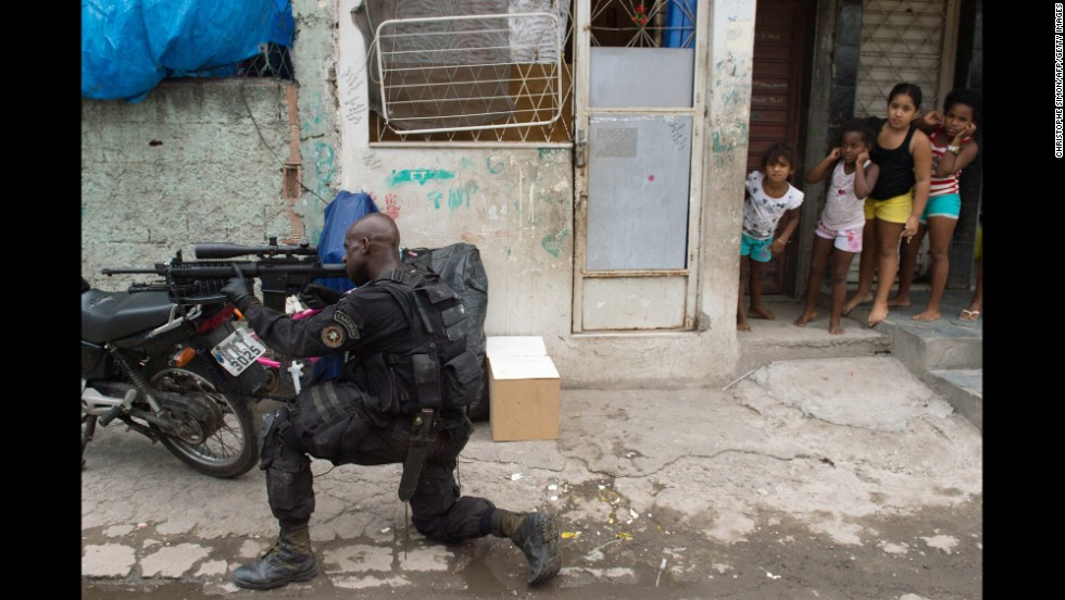 Girls watch a paramilitary police sniper secure an area in the favela as Brazilian soldiers conduct a search for weapons. The shantytown is just a few kilometers from Rio's international airport, where many of the expected 600,000 international fans will land.