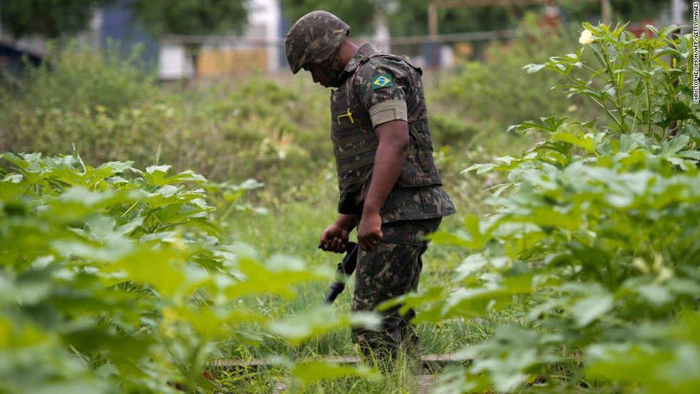 A Brazilian soldier with a metal detector searches for buried weapons in the favela.
