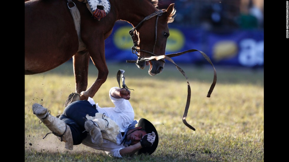 A gaucho is unseated by a wild horse Tuesday, April 15, during the annual Criolla Week celebrations in Montevideo, Uruguay.