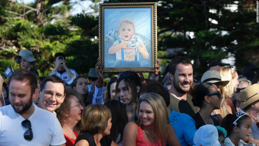 A woman holds up a painting of Prince George before the royal couple's visit to Manly Beach.