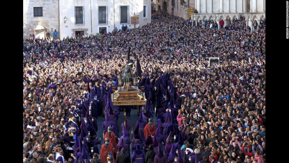"Penitents, surrounded by several thousand people in Cuenca, Spain, carry a statue of Our Father Nazarene during the Good Friday procession ""Way of Calvary."""