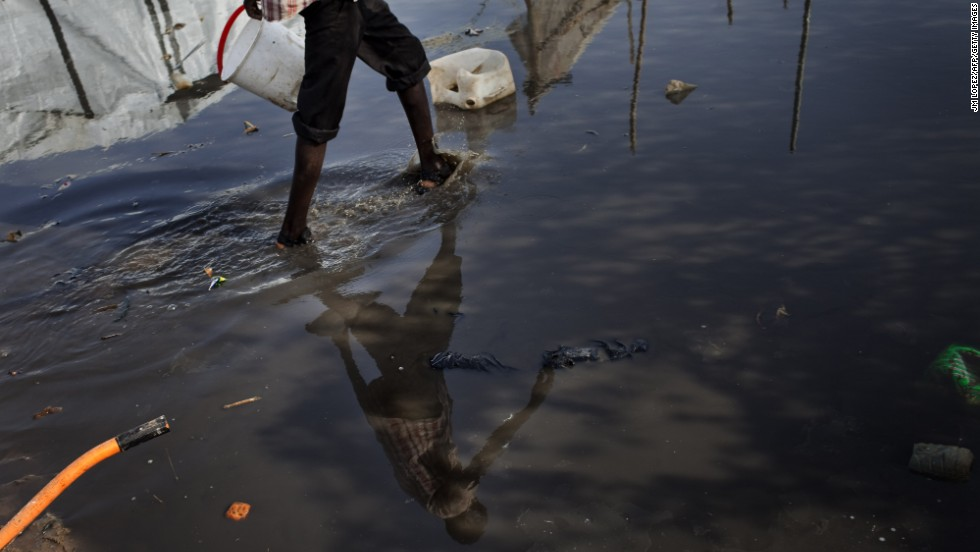 A South Sudanese man walks in a puddle Saturday, March 15, at a camp for internally displaced people.