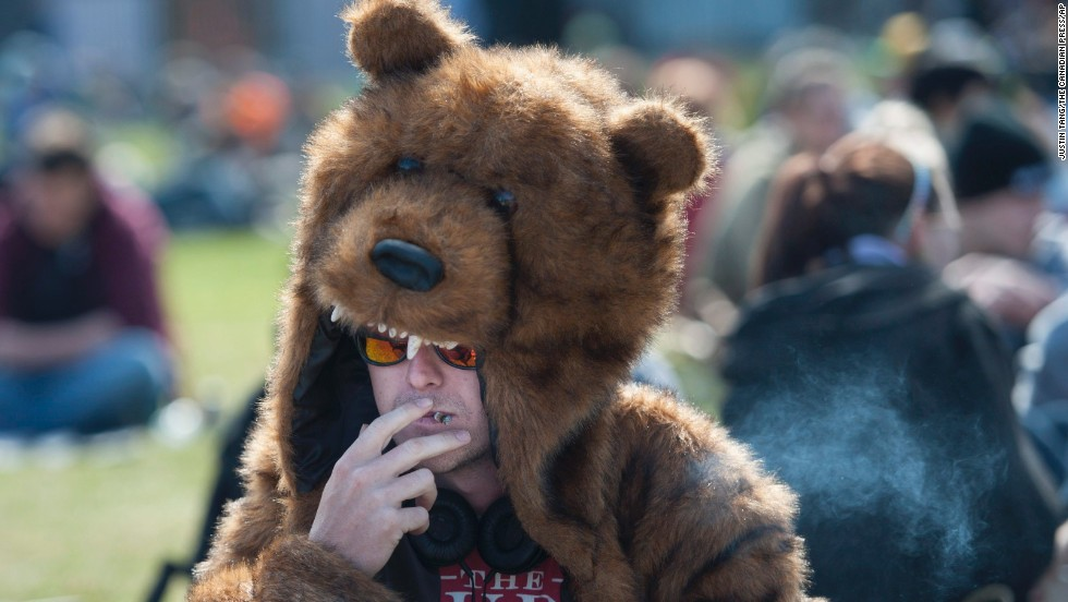 A man in a bear costume smokes a joint on April 20 at the Fill the Hill marijuana rally on Parliament Hill in Ottawa.