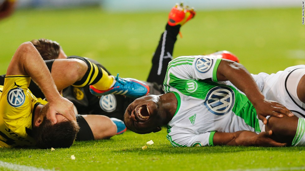 Dortmund's Sokratis, left, and Wolfsburg's Bernard Malanda-Adje lie injured during the German soccer cup semifinal match on April 15 in Dortmund, Germany.