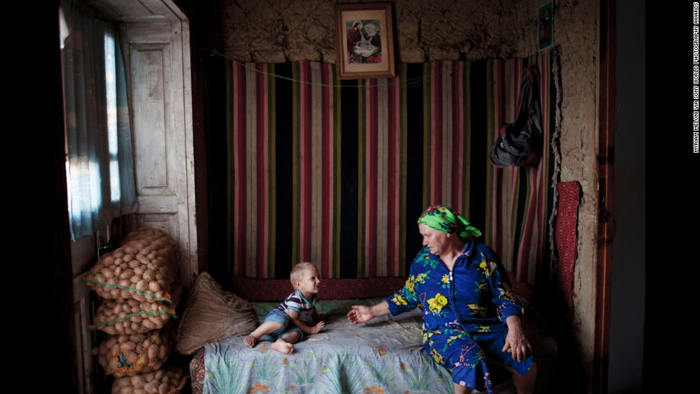 "Italian photographer <a href=""http://www.myriammeloni.com/"" target=""_blank"">Myriam Meloni</a> won the Lifestyle category for her work in Moldova, where she photographed families impacted by migration. The woman in this photo cares for her three grandchidlren because her daughter moved abroad in search of work opportunities. ""I was attracted by the gesture of love and complicity between them,"" she said."