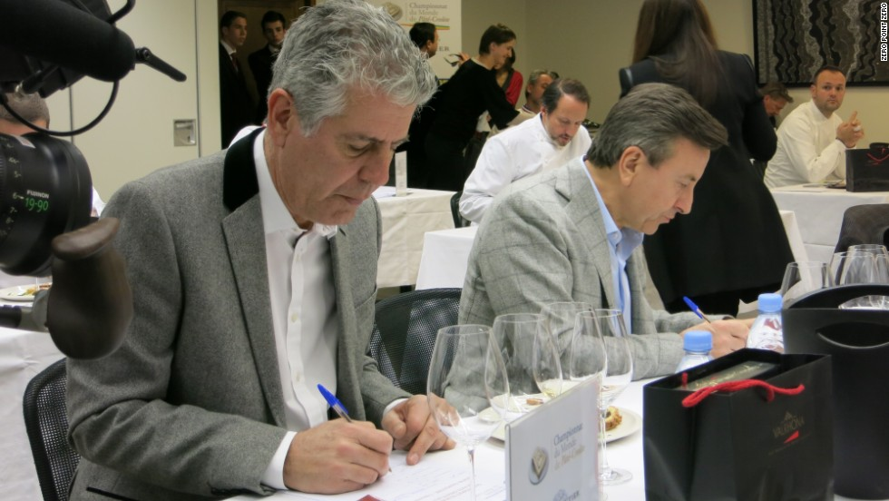 Bourdain, left, and Boulud fill out judging ballots at the Championnat du monde de Pate-Croute, hosted at Maison Chapoutier.