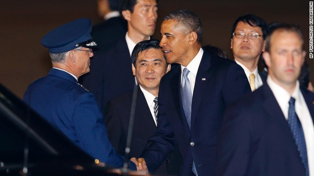 U.S. President Barack Obama is greeted by an unidentified official upon his arrival at Haneda International Airport in Tokyo, Wednesday, April 23, 2014.