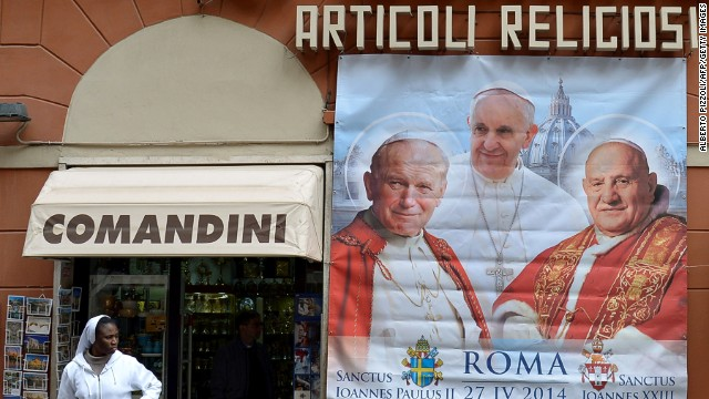 Poster showing Pope John Paul II (left) and Pope John XXIII (right), who are to be canonized by Pope Francis (center) on April 27, 2014.