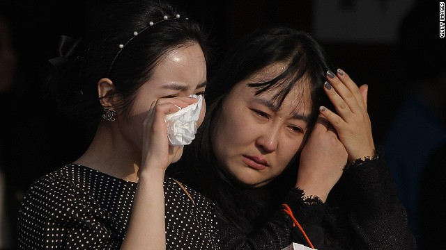 ANSAN, SOUTH KOREA - APRIL 23: South Korean mourners weep after tribute at a group memorial altar for victims of sunken passengers ship at the Ansan Olympic Memorial Hall on April 23, 2014 in Ansan, South Korea. At the altar, Friends and relatives are able to pay tribute to those who have passed in the April 16 ferry disaster off of Jindo Island in South Korea. The confirmed death toll now reached 130, and more than 170 people are still missing, as reported. (Photo by Chung Sung-Jun/Getty Images)