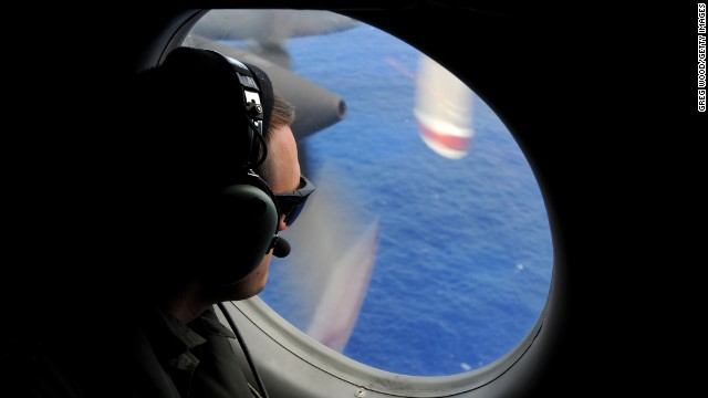 A crew member of a Royal New Zealand Airforce (RNZAF) P-3K2-Orion aircraft helps to look for objects during the search for missing Malaysia Airlines flight MH370 in flight over the Indian Ocean on April 13, 2014 off the coast of Perth, Australia. S