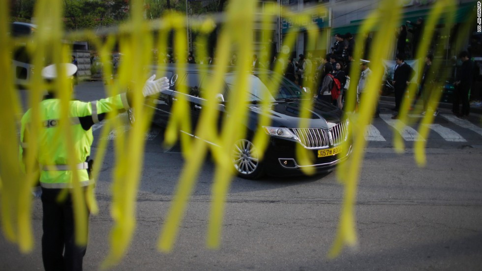 Yellow ribbons honoring the victims flap in the wind as a hearse carrying a victim's body leaves Danwon High School in Ansan on April 24. Most of the people on board the ferry were high school students on their way to the resort island of Jeju.