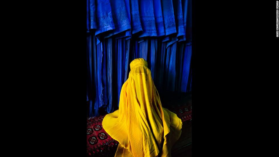 An Afghan woman wears a canary burqa in Kabul, 2002.
