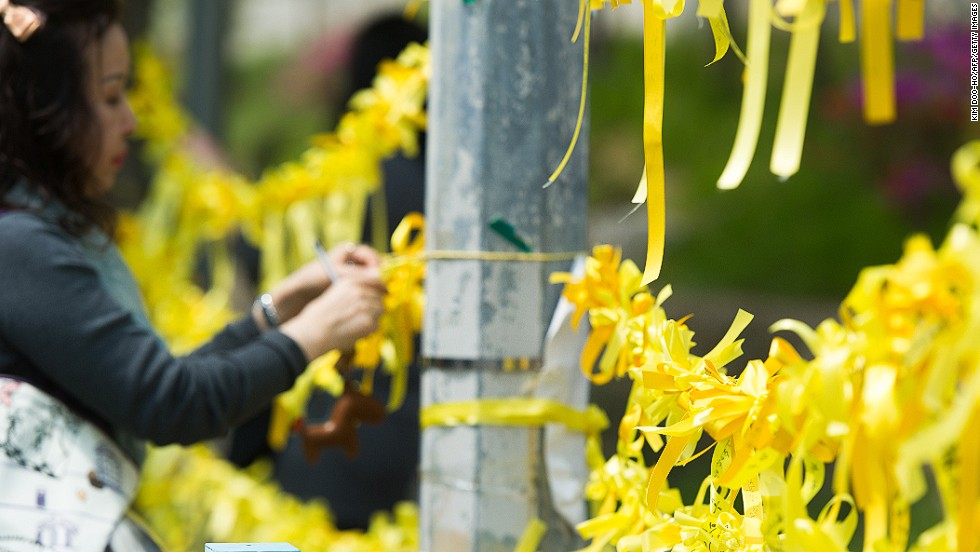 "APRIL 24 - ANSAN, SOUTH KOREA: A woman ties <a href=""http://cnn.com/2014/04/24/world/asia/south-korea-yellow-ribbons/index.html"">yellow ribbons</a>, symbolizing hope for the safe return of missing passengers on the ""Sewol"" ferry, onto a main gate of Danwon High School. More than 300 students from the school were on a field trip on the ferry that sank last week off the coast of South Korea."