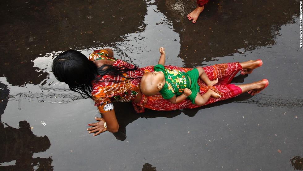 An infant lies on the back of a woman during a ritual as she worships Sheetala Mata, the Hindu goddess of smallpox, during the Sheetala Puja in Kolkata, India, on  Saturday, April 19.