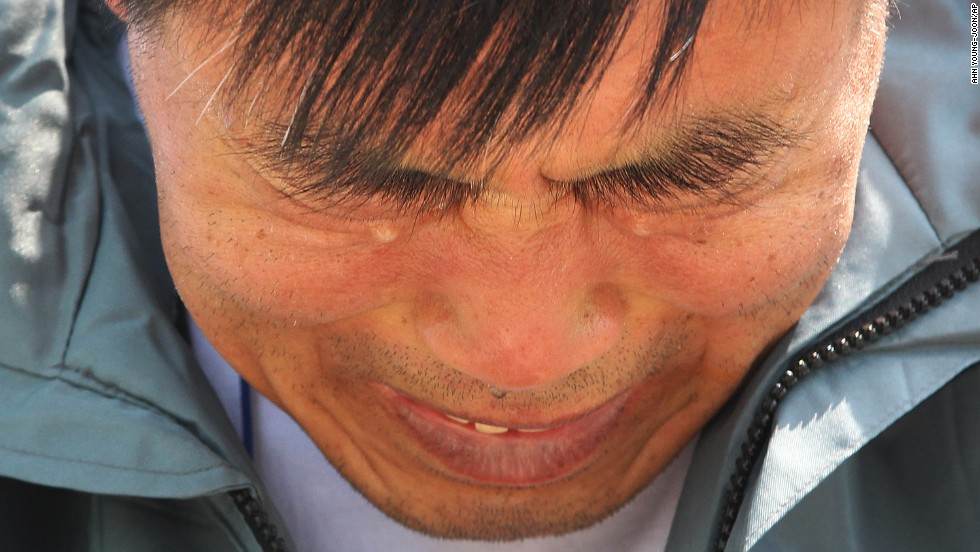 A relative of a passenger weeps while waiting for news of his missing loved one at a port in Jindo on April 25.