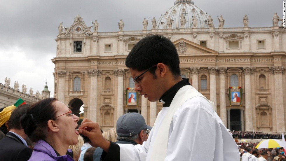 A priest gives Holy Communion to a woman in St. Peter's Square at the Vatican on April 27.
