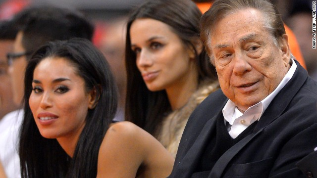 Los Angeles Clippers owner Donald Sterling, right, and V. Stiviano, left, watch the Clippers play the Sacramento Kings during the first half of an NBA basketball game in Los Angeles, on October 25, 2013.