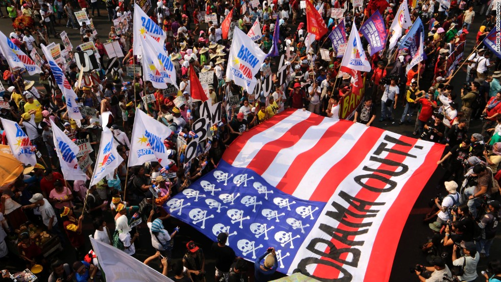 Protesters carry a mock U.S. flag and shout anti-U.S. slogans during a protest of President Obama's visit to the Philippines on April 28.