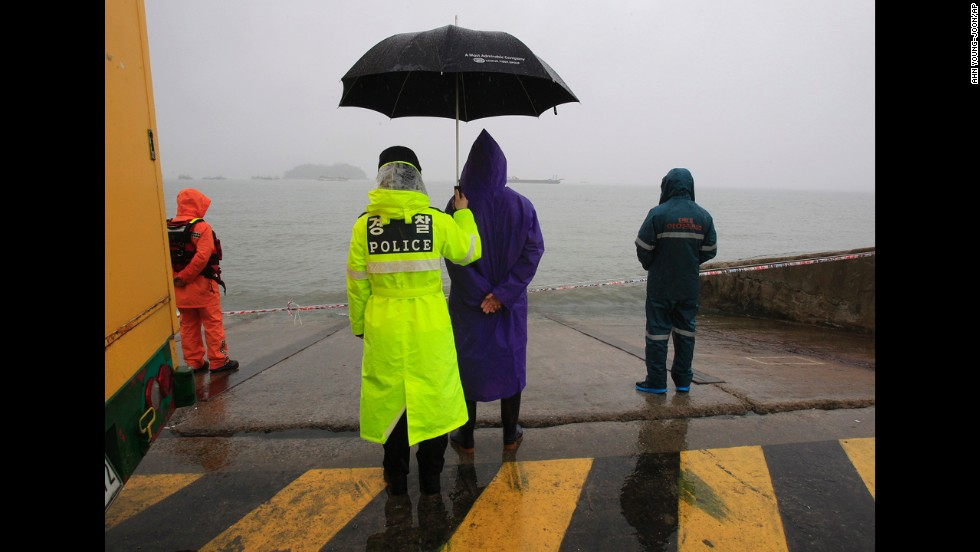 A police officer holds an umbrella for a relative of a missing ferry passenger Monday, April 28, in Jindo, South Korea.