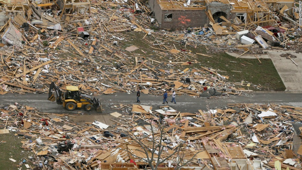 People walk between destroyed houses on April 28 in Mayflower.