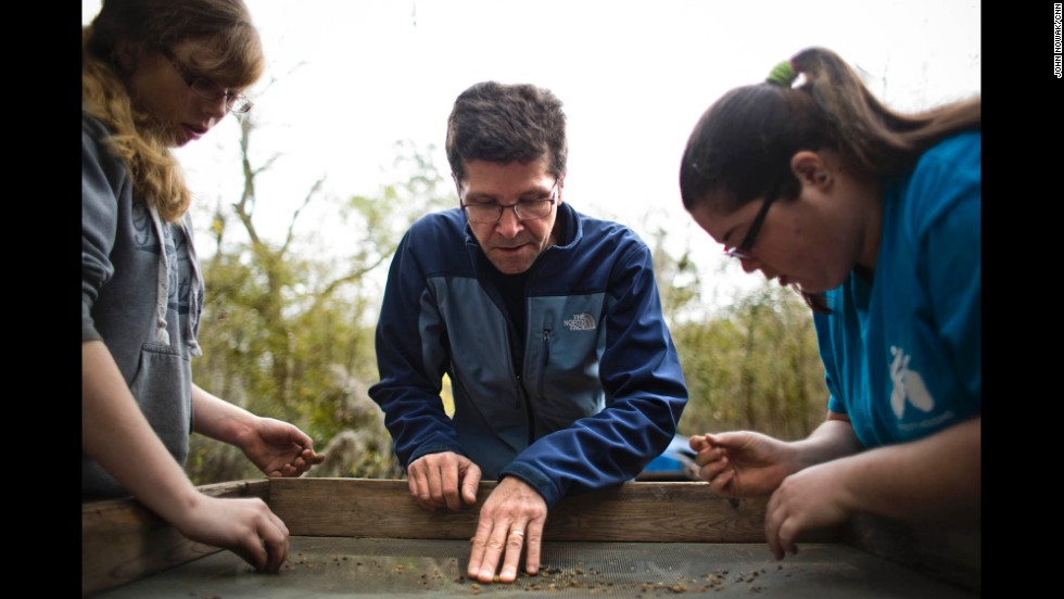 Lance Greene, an assistant professor at Georgia Southern University, looks over sediment being sifted by students Heather McNamee, left, and Victoria Simpson during an excavation at the site of Camp Lawton, a large Civil War prison built just north of Millen, Georgia. Greene says the archaeological effort is aimed, in part, at trying to learn more about the grouping and ethnicity of Union prisoners who were housed there in late 1864.