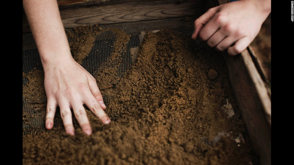 """Georgia Southern student Heather McNamee sifts dirt during an excavation dig. """"It's really hard,"""" she said of locating artifacts in piles of earth. """"If you're wearing gloves, sometimes you have to take them off. It's a feeling thing."""" She took part in a dig that was interrupted by rain in late March."""