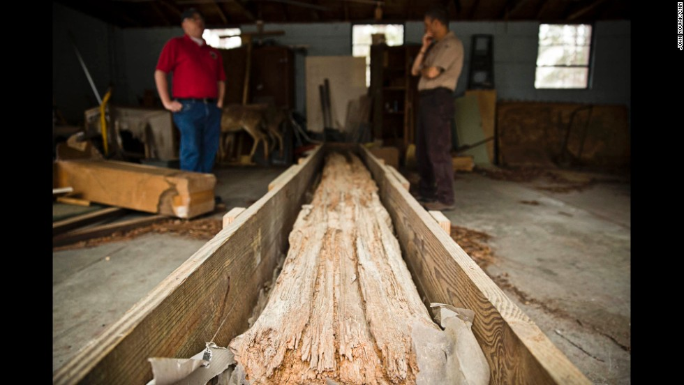 A massive timber log rests on the site of a now-closed hatchery where prisoners once lived. The log is believed to be one of the few remaining pieces of the original stockade wall, which encompassed a 1-mile perimeter around the prison. Kevin Chapman, left, a former Georgia Southern student who did extensive research at Lawton, and archeologist Rick Kanaski work for the U.S. Fish and Wildlife Service, which operates hatcheries. Part of Camp Lawton was built on property now belonging to the federal government.