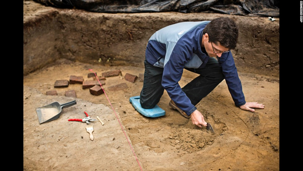 "Greene uses a trowel in an opened area where a prisoner ""shebang,"" or shelter, once stood. Behind him are bricks that were likely ""liberated"" by Union soldiers from a camp oven. They were likely used to support the walls of the shebang. The Georgia Southern team is excited about this feature, and have found evidence of a fire perhaps used for warmth."