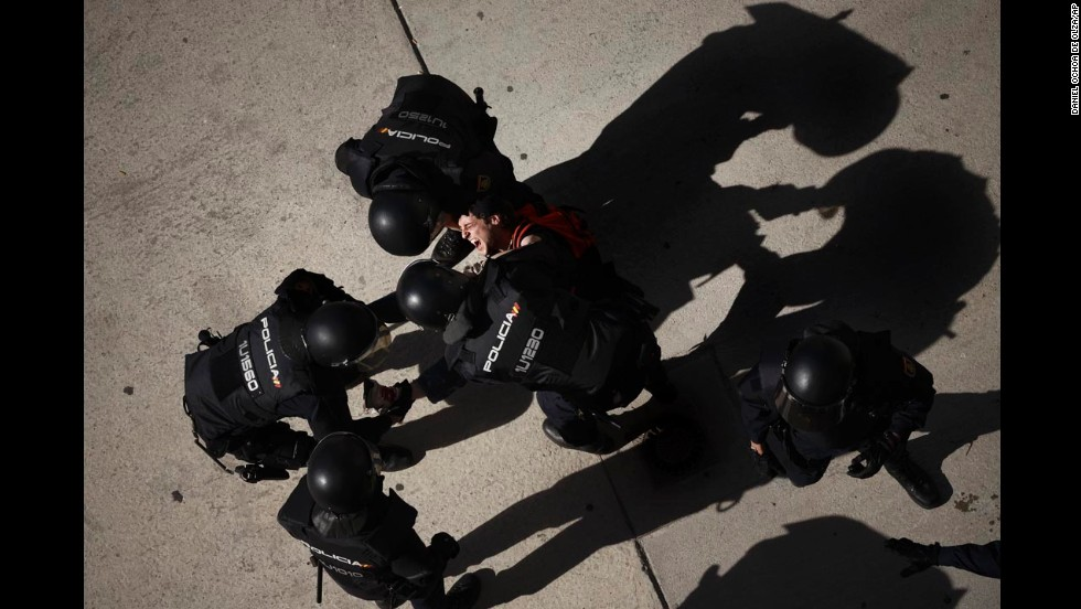 A member of the Victims' Mortgage Platform is carried away by riot police officers after he tried to block a woman's eviction in Parla, Spain, on Wednesday, April 30. Evictions have been common in many parts of Spain, which has been struggling with a recession and unemployment.
