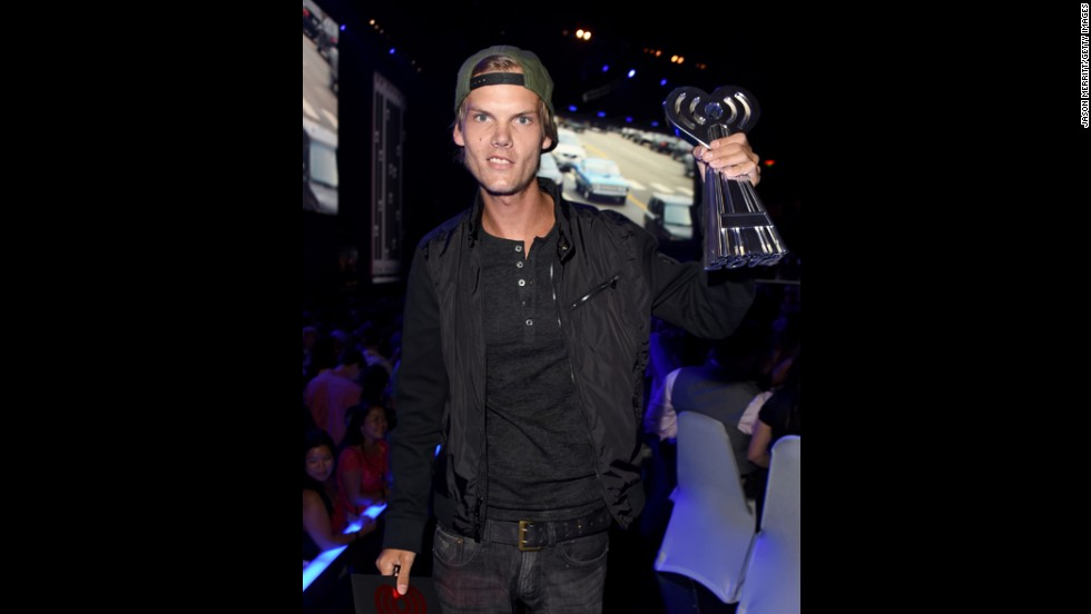 DJ Avicii shows off his award as he walks backstage.