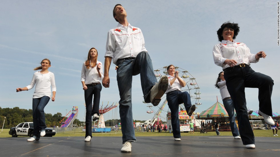 """Rocky Top"" has become ingrained among thousands of Tennesseans, from the Smoky Mountains in the east to the western bluffs along the Mississippi River. Kelly Lovelace, 24, center, kicks it to the tune of ""Rocky Top"" with the Riverboat Cloggers during the 2012 Bartlett Festival and Car Show."