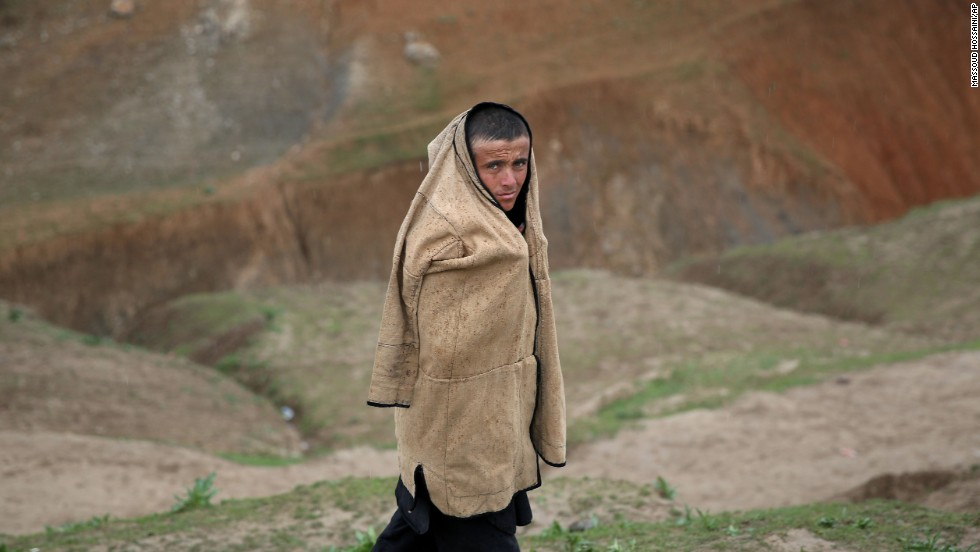 An Afghan teenager protects himself from the rain as he walks near the site of the landslide on May 4.