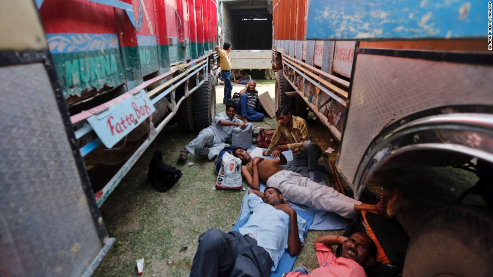 Election officers rest between parked trucks before proceeding to their polling stations May 6 in Allahabad, India.