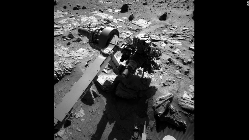 An arm of Curiosity drills two holes into sandstone on May 5. The rock powder collected will be analyzed by the rover's onboard instruments.