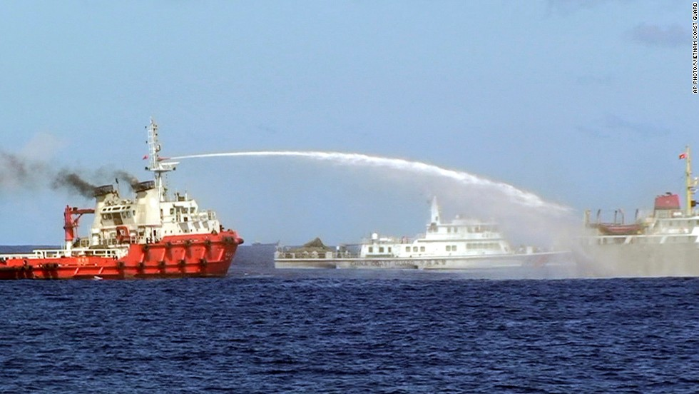 In this photo released by the Vietnam Coast Guard, a Chinese ship, left, shoots water cannon at a Vietnamese vessel, right, while a Chinese Coast Guard ship, center, sails alongside in the South China Sea, off Vietnam's coast, Wednesday, May 7, 2014.