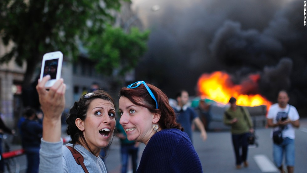 Tourists take a selfie as demonstrators burn a trash container during a May Day rally in Barcelona, Spain, on Thursday, May 1. May Day is also known as International Workers' Day, and tens of thousands of workers in European cities marked the occasion with a mix of anger and gloom over austerity measures meant to contain the eurozone debt crisis.