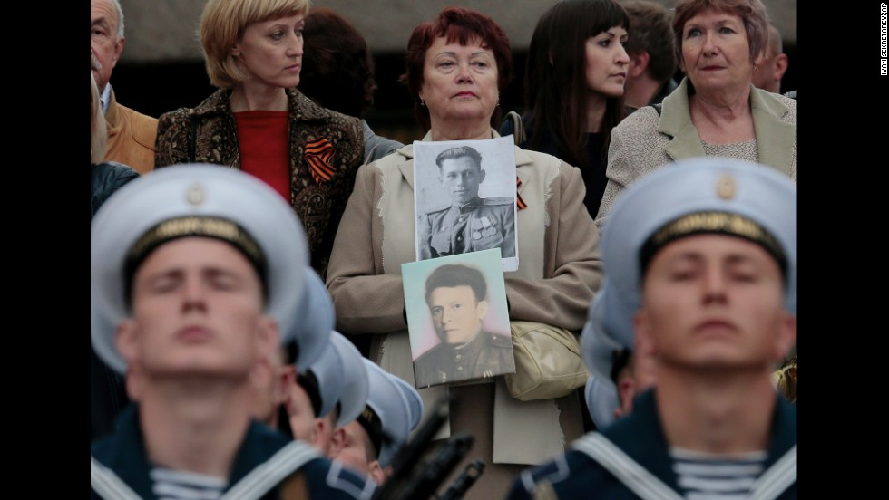 At a parade in Sevastopol, Crimea, a woman holds portraits of her relatives who served in the Soviet Army and died during World War II.