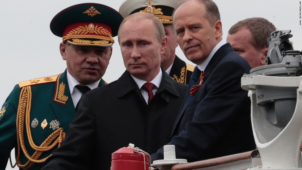 Russian President Vladimir Putin, flanked by Defense Minister Sergei Shoigu, left, and Federal Security Service Chief Alexander Bortnikov, right, arrives at a Victory Day celebration after inspecting battleships in Sevastopol.