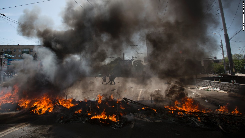 Black smoke billows from burning tires used to prevent government troops' armored personnel carriers from passing through in Mariupol on Saturday, May 10.