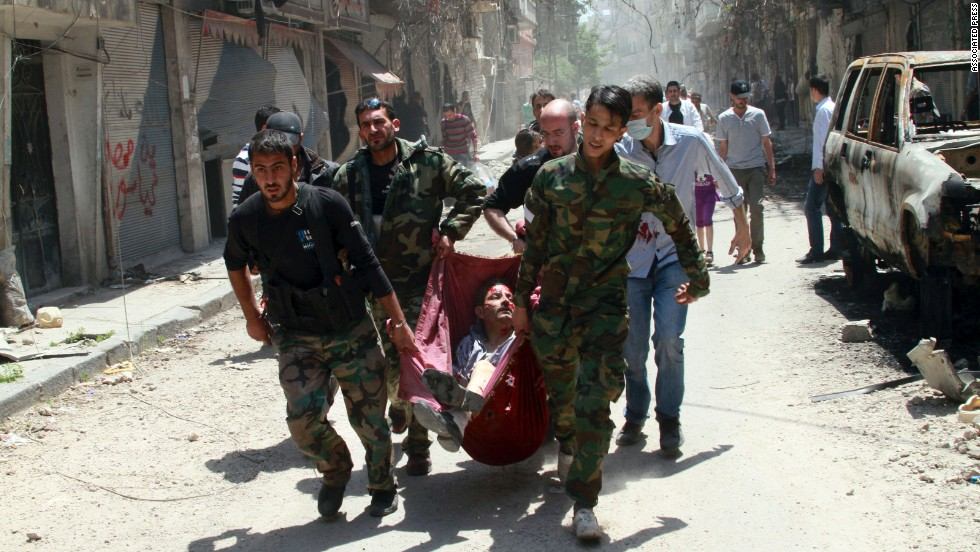 Rescuers carry a man wounded by a mine in the Bustan al-Diwan neighborhood of Homs on May 10.